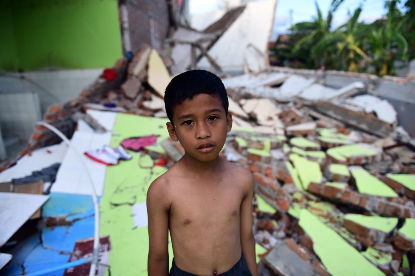 A boy stands among the ruins of a building destroyed by the recent tsunami in Palu, Indonesia.