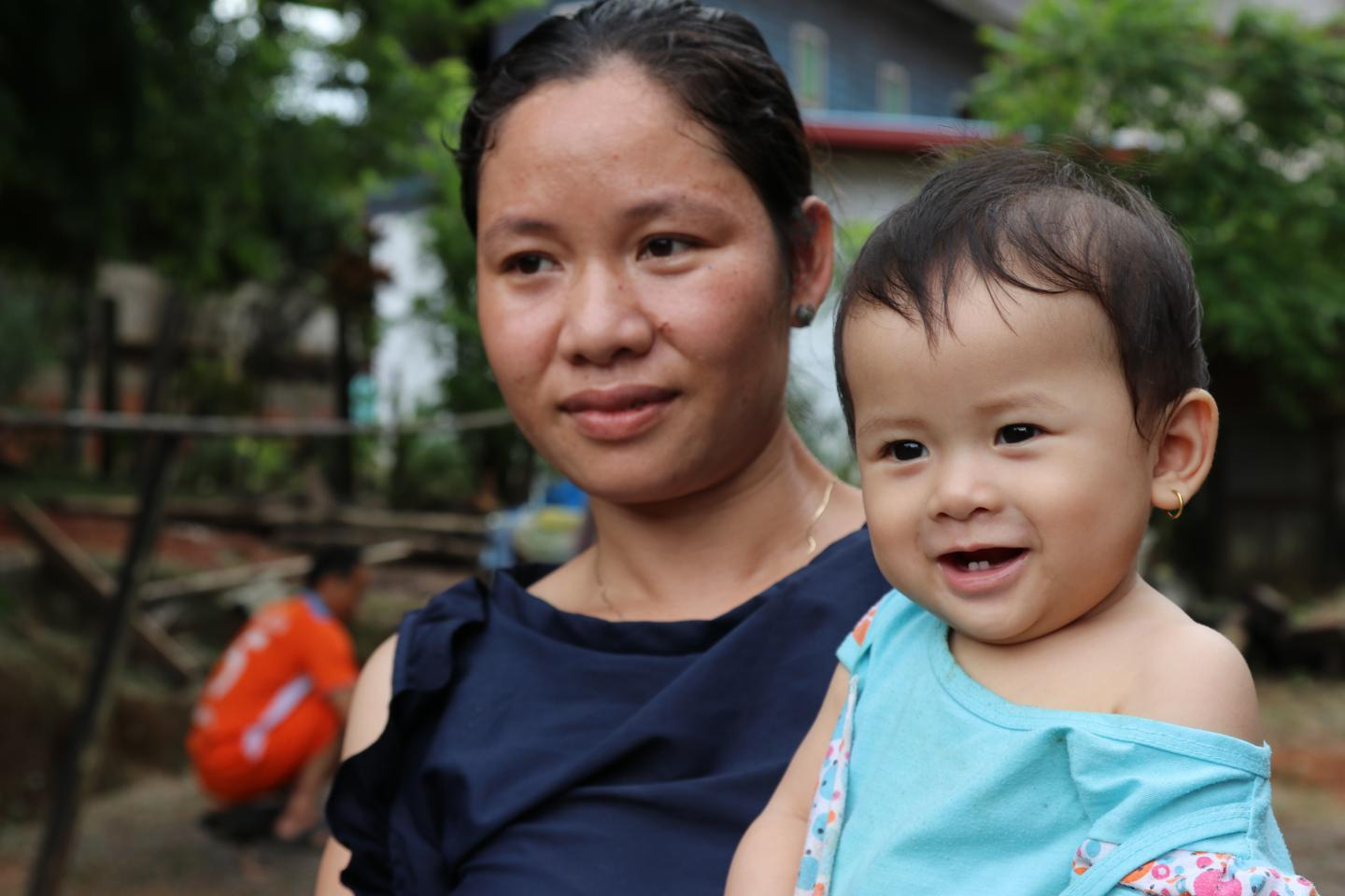 A mother holds her smiling daughter, Lao PDR