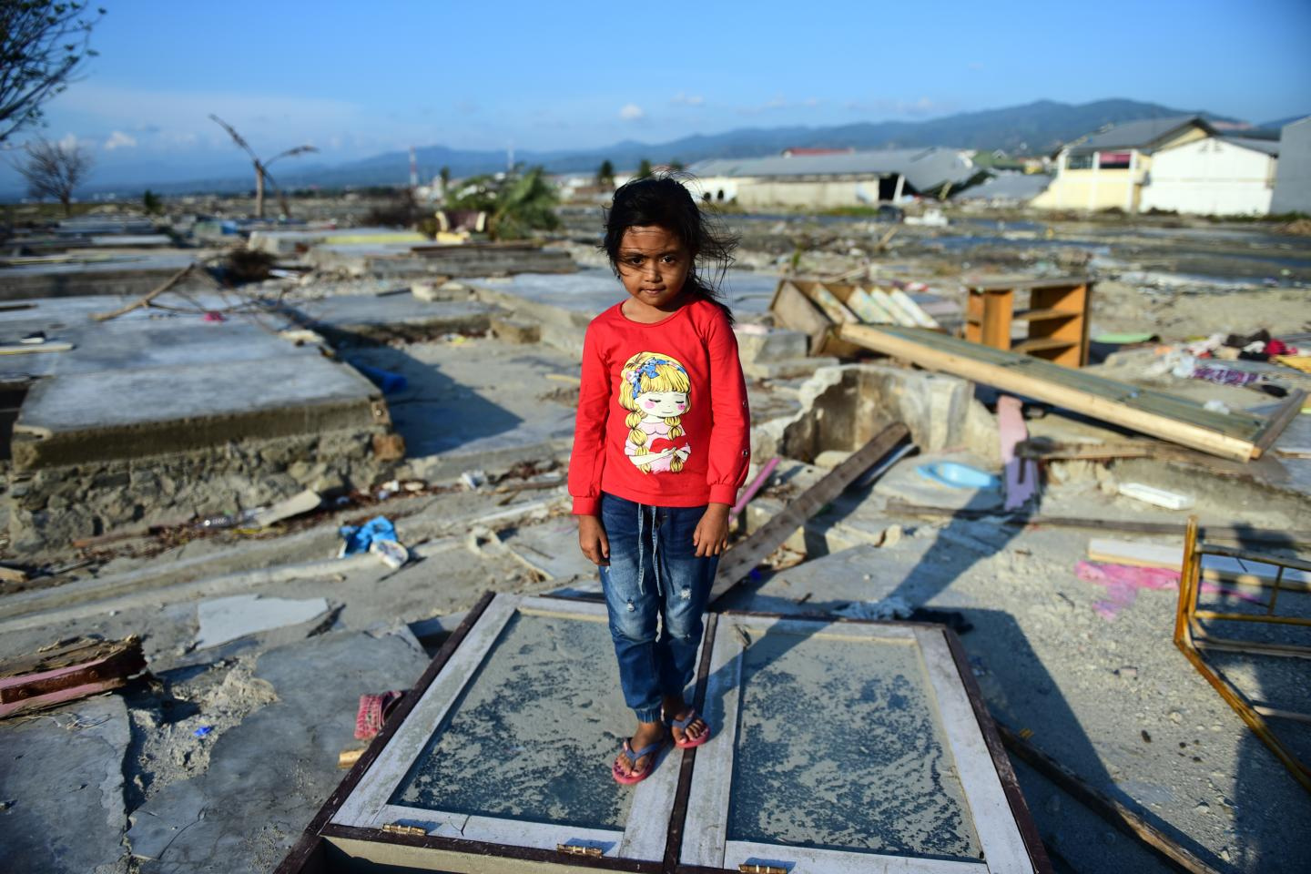 A girl stands among the ruins of her home which was destroyed by the 28 September earthquake and tsunami in Indonesia.