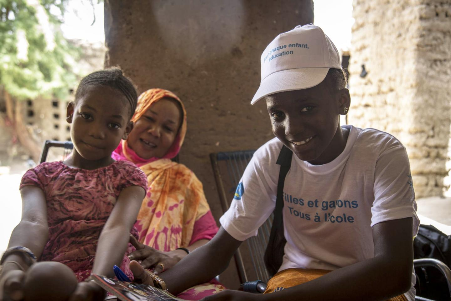 A girl in a UNICEF shirt smiles next to a mother and daughter, Mali