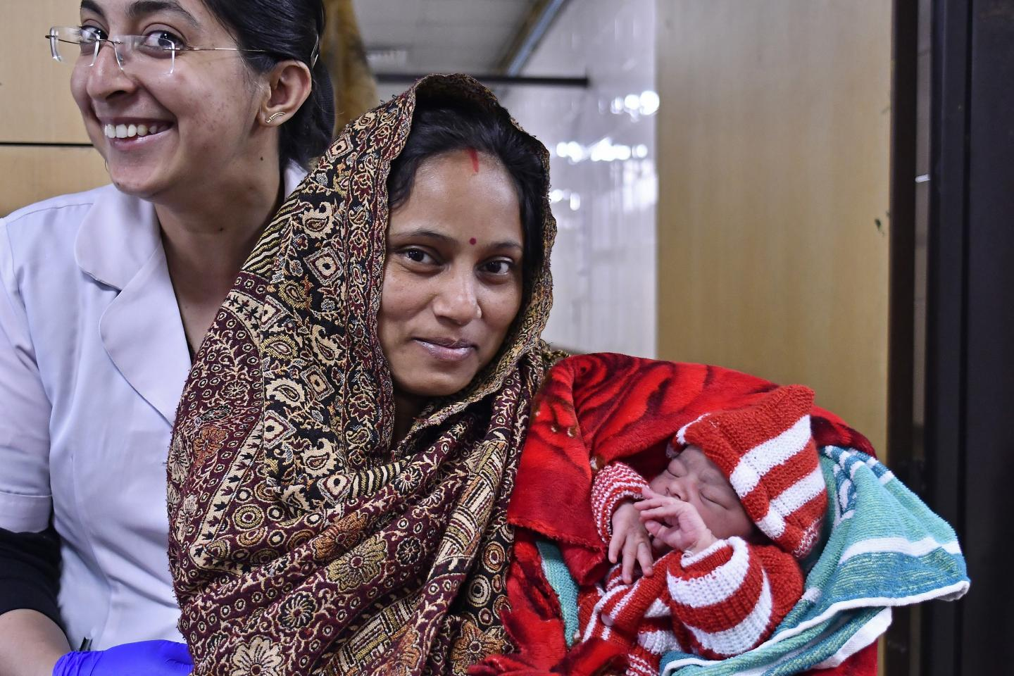 India. A mother holds up her newborn baby girl at Lady Hardinge Medical College in New Delhi.