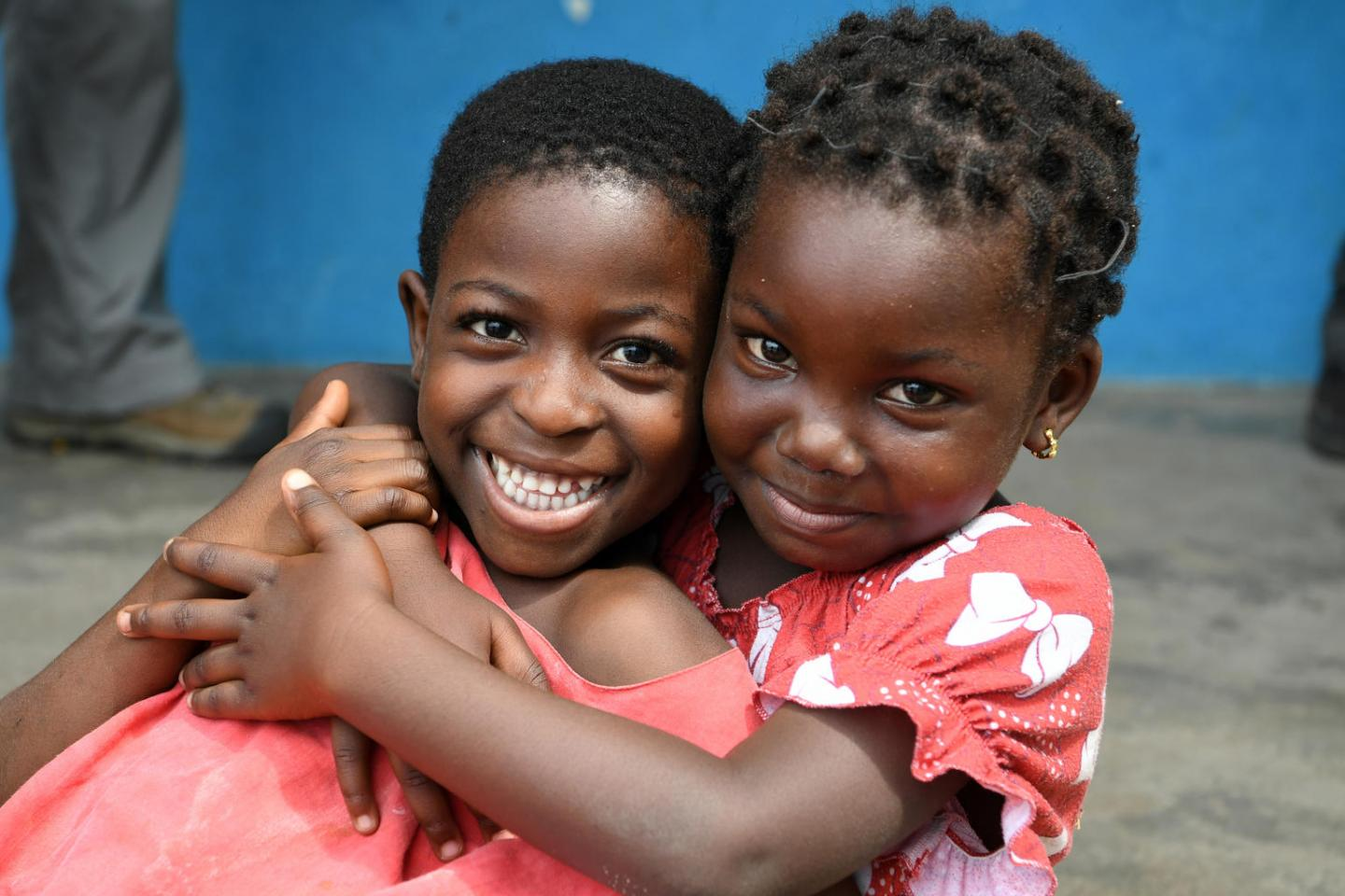 Girls in Abidjan, Côte d'Ivoire, embrace each other with smiles.