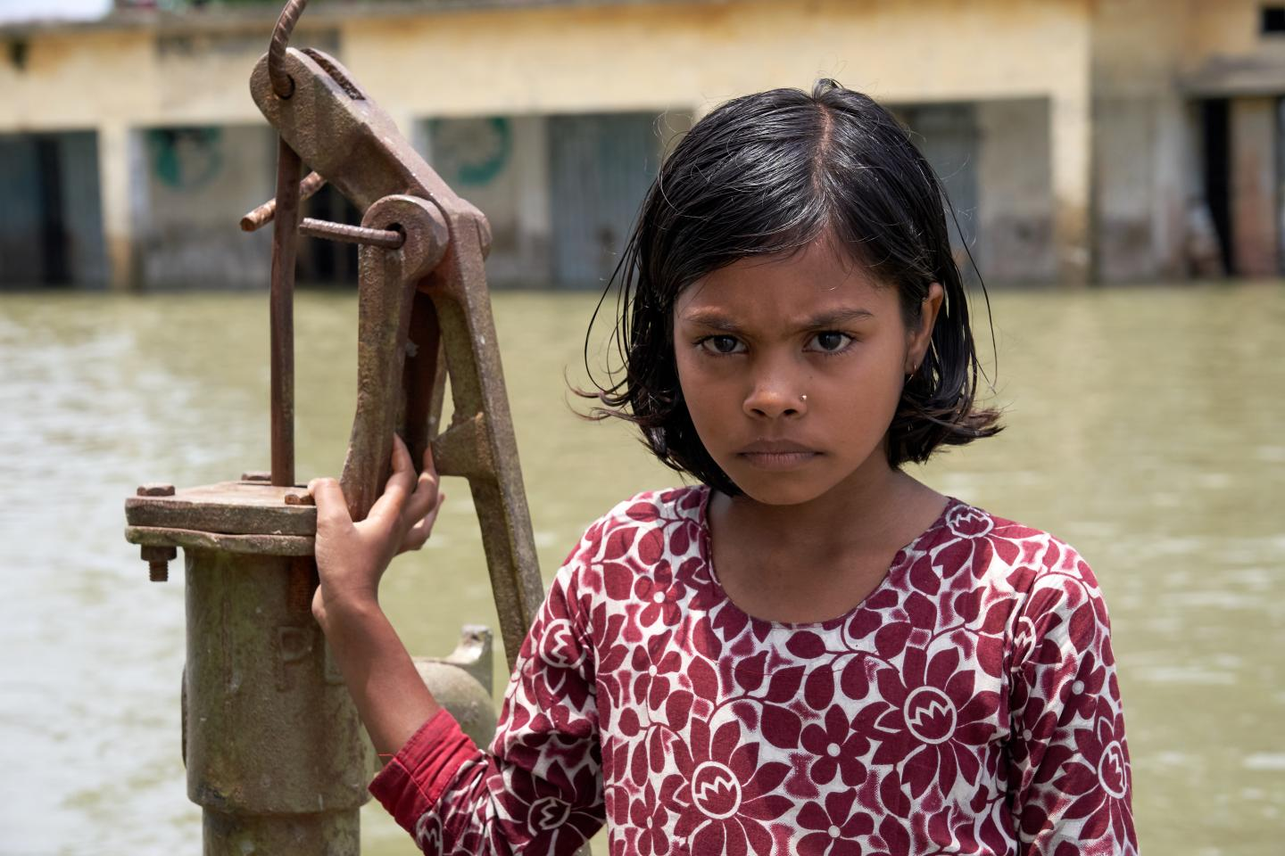 A girl stands in floodwater in front of a well, Bangladesh