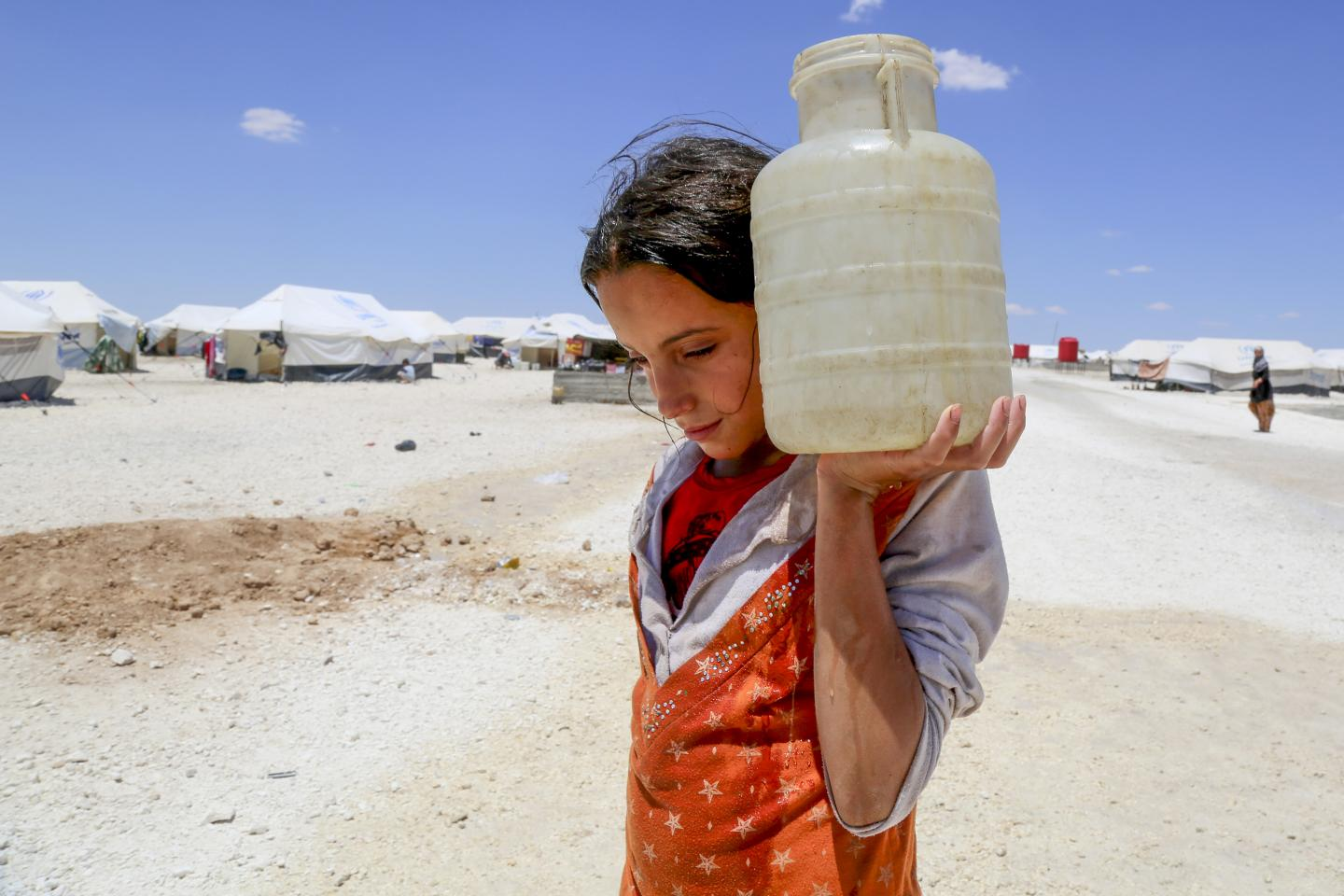 A girl carries water in a refugee camp, Syria
