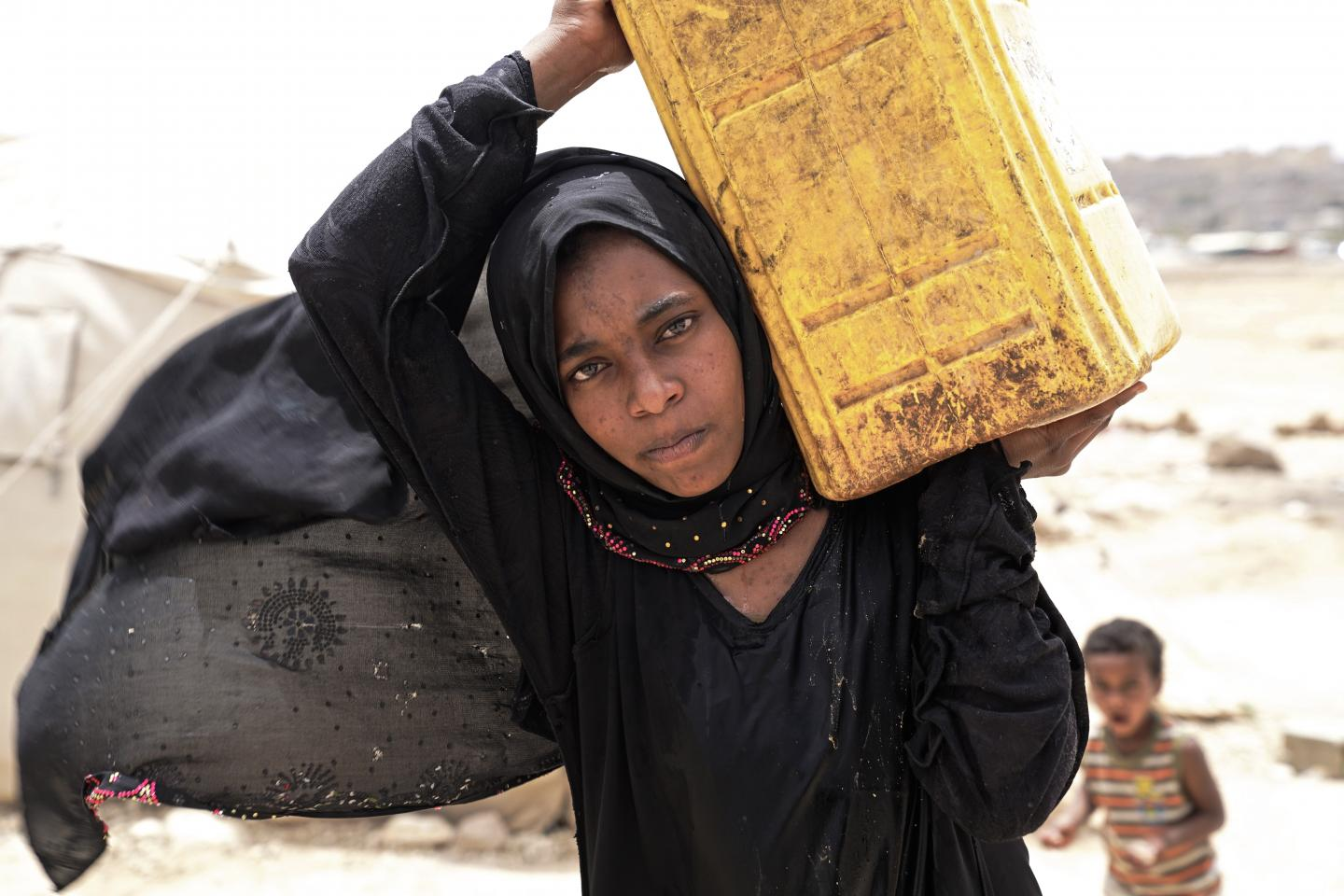 A girl carries a jerry can on her shoulder, Yemen