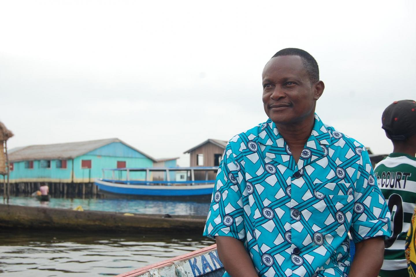 Benin, West Africa: a man is sitting on a boat looking at the horizon.