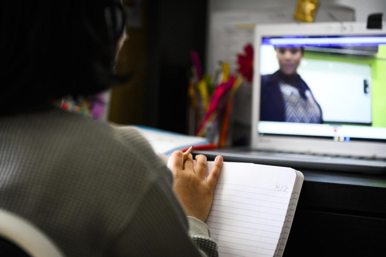 فتاة تدون ملاحظات أثناء فصل دراسي عبر الإنترنت على جهاز الكمبيوتر في المنزل.
