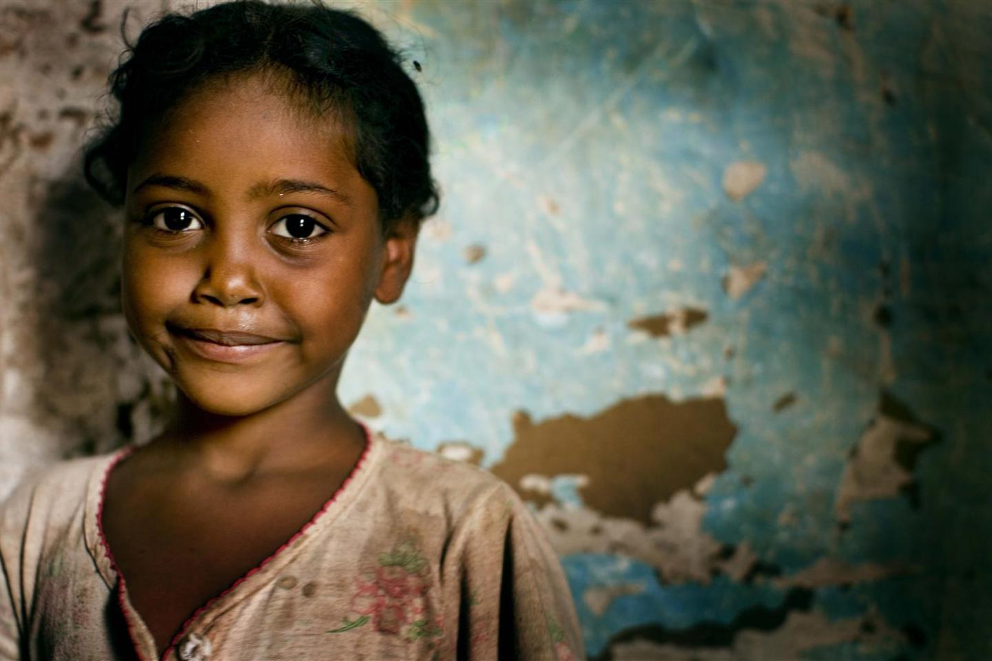 A girl, 5, stands in her home in Aroma Village, near the city of Kassala.