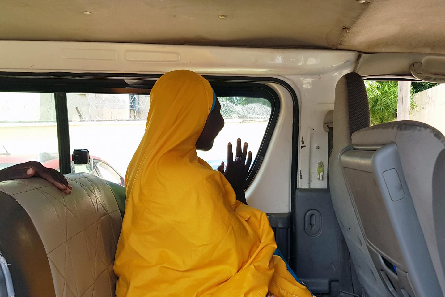 A girl waves out a van window, Nigeria