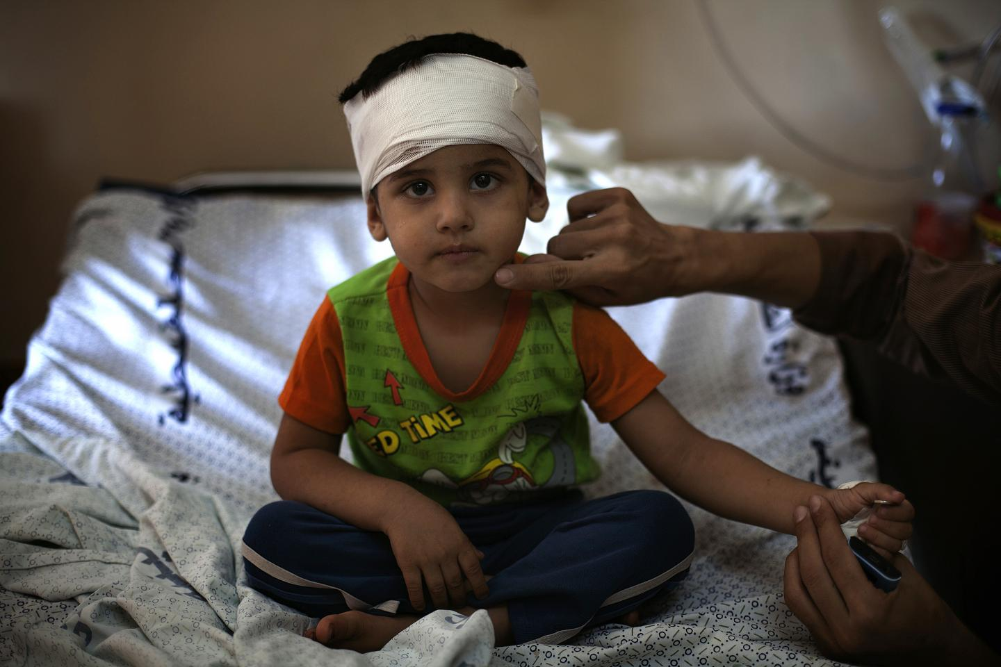 A little boy sits on a hospital bed, his head wrapped in bandages.