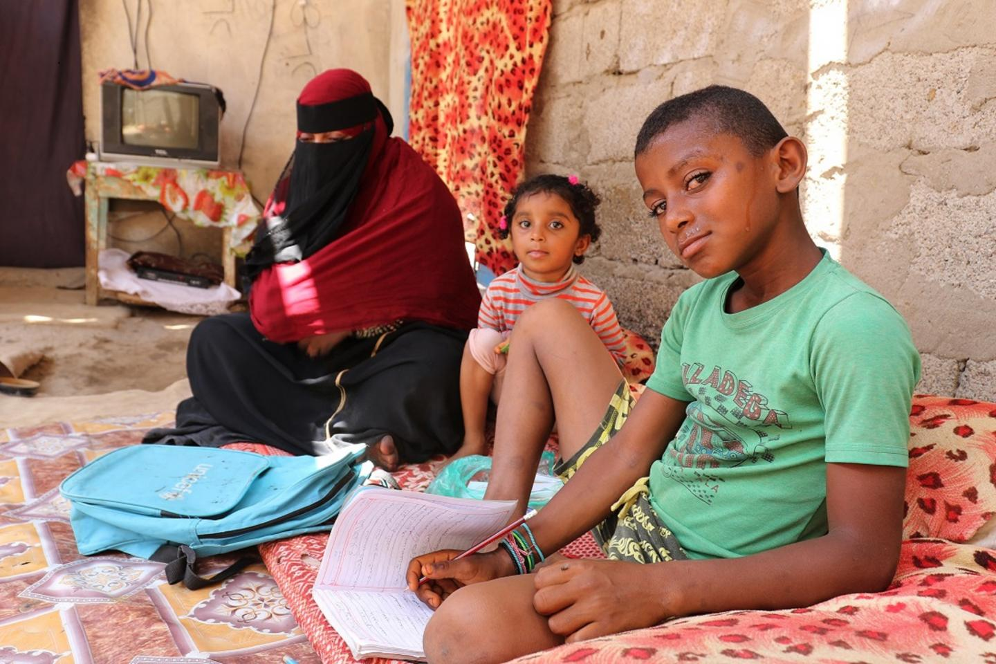 A woman sits with two children, Yemen