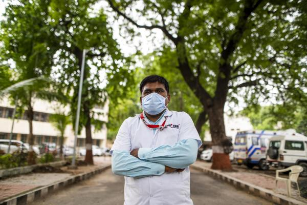 Health worker Pravinsinh S Baria stands as he awaits a case to be assigned in Godhra in Godhra, Gujarat, India.