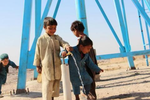 Children wash up and drink from a faucet, Afghanistan