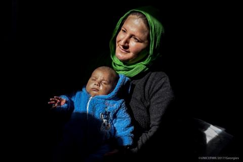 A woman holds her child on her lap, former Yugoslav Republic of Macedonia