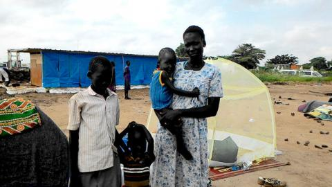 Maria and her children stand in front of the rudimentary shelter