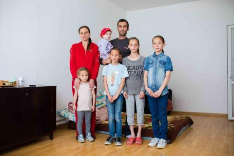 The Ferenzes: Cătălina Andreea, 6, Loredana, 36, Elena Claudia, 2, Miruna, 9, Ioan, 47, Georgiana Alina, 13, and Ionela Raluca, 12, photographed in their new apartment, after their house burned down.