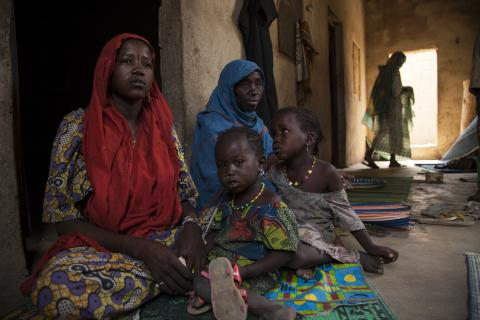 Residents of a so-called widows' house in Banki, Borno State, north-east Nigeria, sit with their children.
