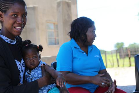 Vivian Ndungati sits with one of the children she cares for
