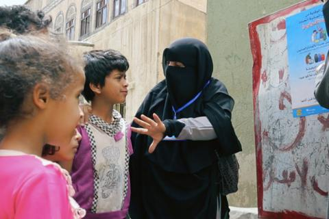 Fathya talks to children at a water point