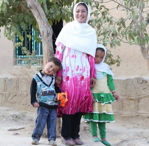 A woman stands with two children, Afghanistan