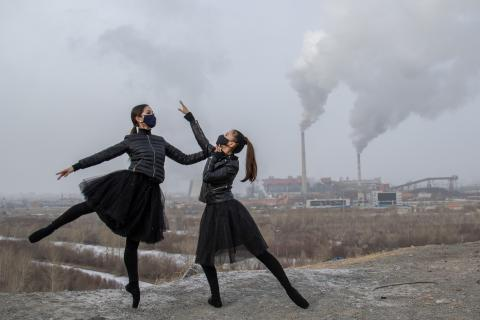 Mongolia: Two ballet dancers wearing masks strike a pose with factory chimneys behind them.