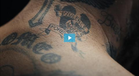 Video still of a tattoo that reads 'Violence Marks Forever'
