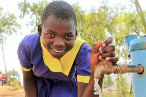 A girl stands next to a water faucet, Malawi