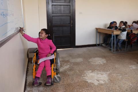 Hanaa, 8, who was paralysed by an exploding bomb and lost the use of her legs, solves a problem on a whiteboard in a classroom at a school in east Aleppo city, Syrian Arab Republic, Wednesday 28 February 2018.