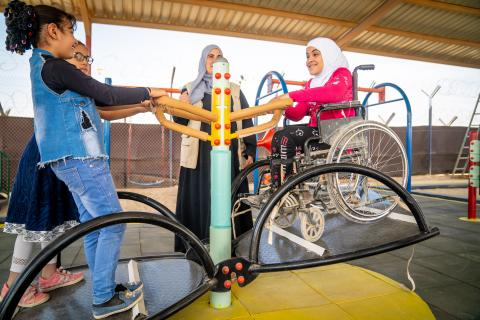Amal, 9 years old, plays on the seesaw in the new inclusive playground in her school in Za'atari Refugee Camp where she is in third grade. She is with Tasneem and Hala, both 10 years old.