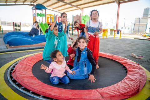 "Tasneem, 10 years old, (front, right) and Asma, 8 years, (front, left) on the trampoline with their friends in the new inclusive playground in her school in Za'atari Refugee Camp. ""I like all of them,"" she says about the new equipment. ""Especially the beanbag. It's so nice to jump on it. I'm so happy."