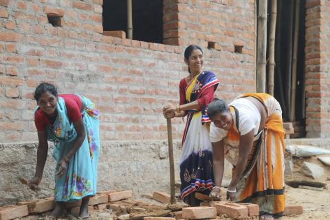 Women work on building a toilet in India