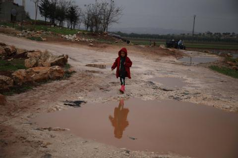 A child walks through a flooded camp in north-west Syria