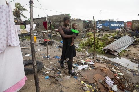 Cecilia Borges carries her son, Fernandino Armindo that is holding a plate, through the destroyed informal settlement, in Beira, Mozambique, on 20 March 2019.