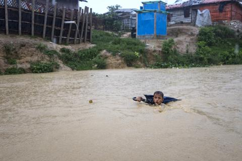On 3 July 2019 in Bangladesh, a young boy navigates a river swollen from days of monsoon rain. He's collecting plastic bottles washed into the river by floods. He sells the plastic to recyclers and uses the money to help his family to purchase vegetables and fish, to complement their diet of rice and dahl.