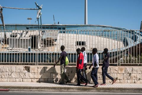 Gambian boys walk past a graveyard of ships used by Libyan Smugglers to transport migrants and refugees to Italy, at port next to a government Hot Spot – a reception center that doubles as a lodging station for unaccompanied minors in Pozzallo, Sicily, on May 17, 2016. In the past boats were captured and sent to these grave yards, but due to the high numbers, today they are burned at sea by the coast guard.
