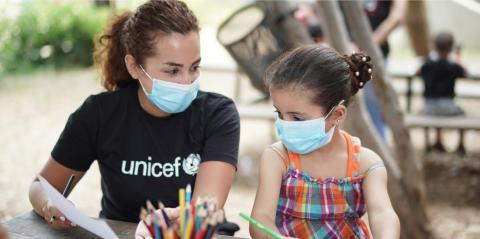 Woman in UNICEF-branded black t-shirt sits with a girl, both wearing face masks