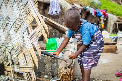 Four-year old Nicky attempts to remove a nail on one of the fallen post from his family's damaged home, on Pentecost Island, Vanuata