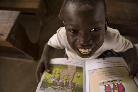 South Sudan. A child smiles in a classroom.
