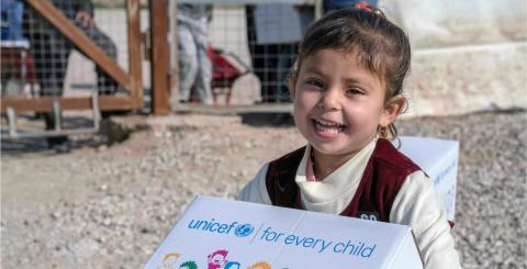 A young girl carries a UNICEF-labelled box