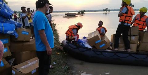 UNICEF-labelled boxes are loaded onto boats