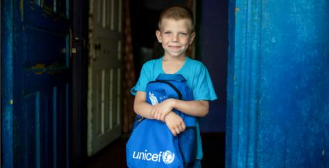 A boy holds a UNICEF-labelled backpack