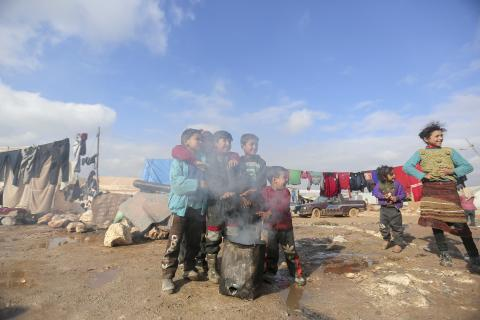 Children gather around a fire to keep warm in Kafr Losin Camp in northwest Syria on 19 January 2021