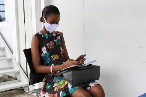 Sierra Leone. A teenager checks her phone.