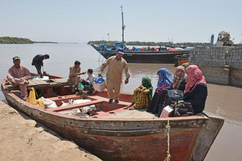 A vaccinator carries a case of vaccines off of a boat, Pakistan