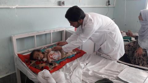Afghanistan. A health worker checks on a small child at a hospital.