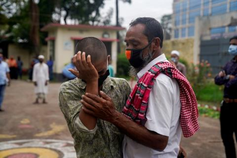 Bangladesh. A man stands with a teenager.