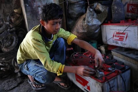 Ten years old, Al Amin works at a garage where he repairs batteries near the Tangail New Bus Stand on 1 February 2014.