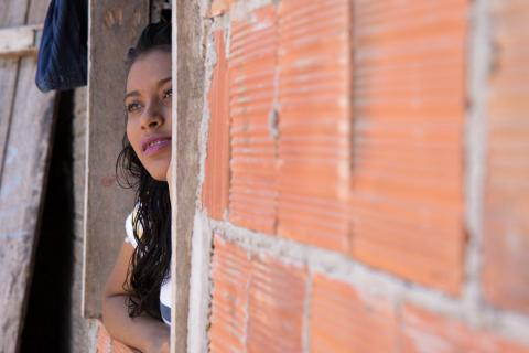 Maria Beatriz (Bia) Teixeira dos Santos looks out the window of her home.