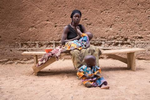 A young woman sits with her two babies, Burkina Faso