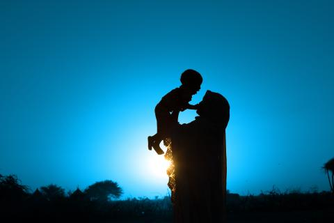A silhouette of a woman lifting up her baby in her village in Ouaddai Region, Sahel belt, Chad.